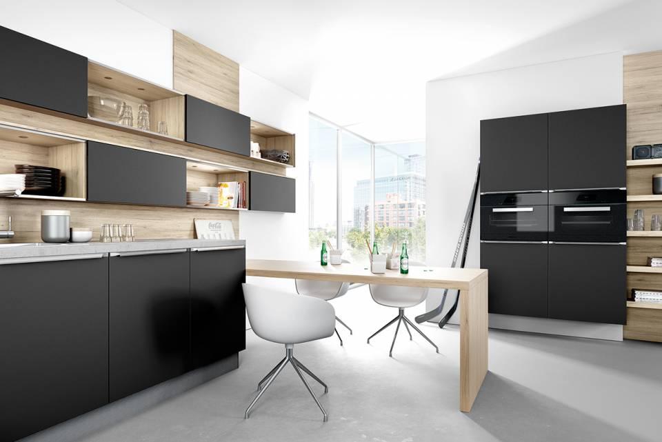 Mattlack in Schwarz, kombiniert mit warmem Holz, setzt in der Küche auffallende Akzente. Absolut im Trend: hoch eingebaute Hausgeräte. Foto: AMK