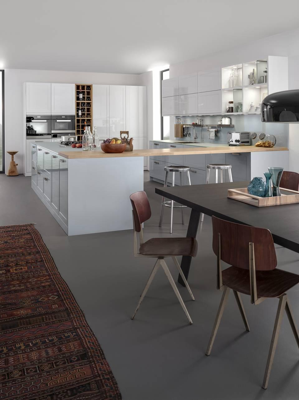Moderne Küchengestaltung mit klassischen, hochglänzend lackierten Rahmenfronten in zwei Farben: Die matte Glasarbeitsplatte sowie das Weinregal in Eiche setzen dazu Kontrapunkte. Fotos: AMK