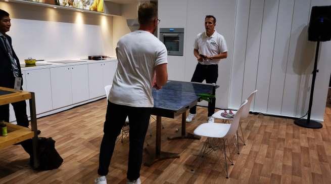 Tischtennisbundestrainer Jörg Roßkopf spielt Tischtennis auf einem Miji Kochtisch.