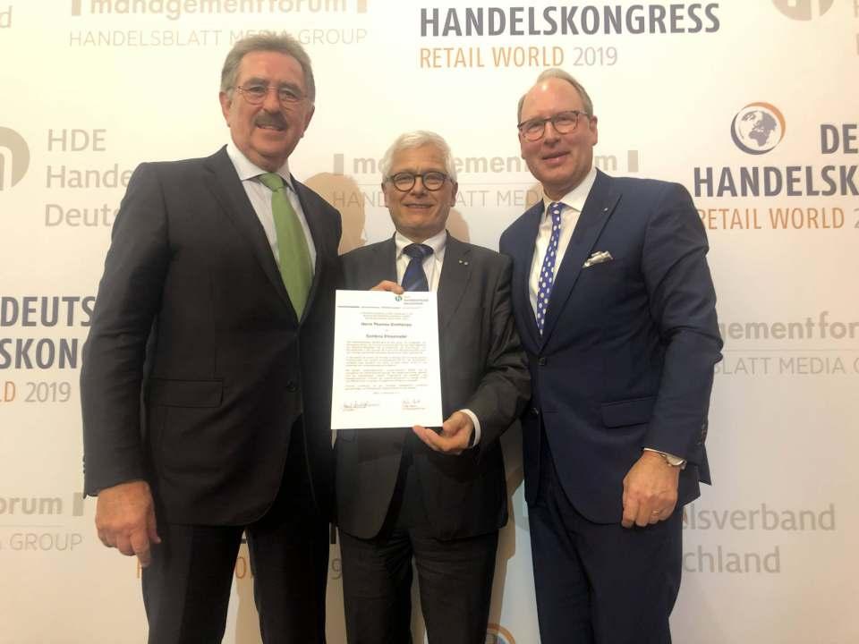 In Berlin überreichten HDE-Präsident Josef Sanktjohanser (l.) und Hauptgeschäftsführer Stefan Genth (r.) die Goldene Ehrennadel an Thomas Grothkopp (M.)