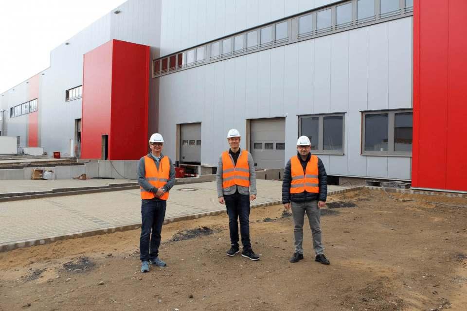 Vor der Fertigstellung: Das neue Brömmelhaupt Logistikzentrum mit (v.l.) Sascha Dittrich, Leiter Operations, Geschäftsführer Robert Drosdek und Logistikleiter Stefan Tsouparidis.