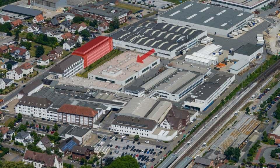 Das rot markierte Gebäude zeigt das geplante Forschungs- und Entwicklungszentrum. Der Pfeil weist auf die Halle (hier noch mit der alten Lichtkuppel) für die neue Pressenanlage.