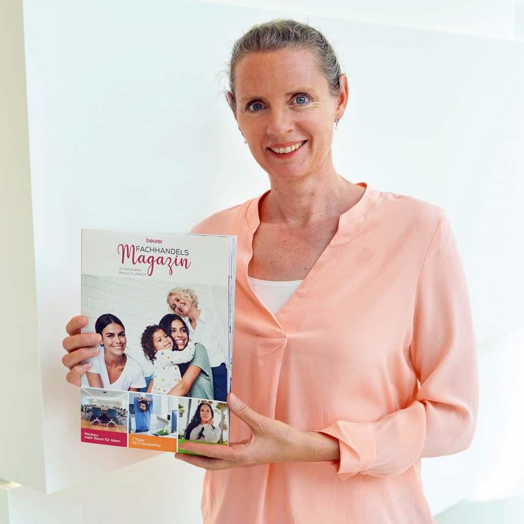 Marketingleiterin Kerstin Glanzer mit der druckfrischen Erstausgabe des Fachhandelsmagazins von Beurer.