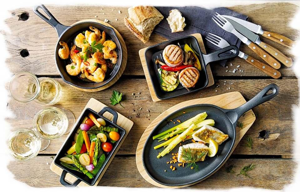 Für die Garnelen, das Gemüse oder den Fisch: In den gusseisernen Pfannen von Küchenprofi lassen sich die Köstlichkeiten zubereiten und servieren. Dann kommt der Untersetzer aus Pinienholz zum Einsatz.