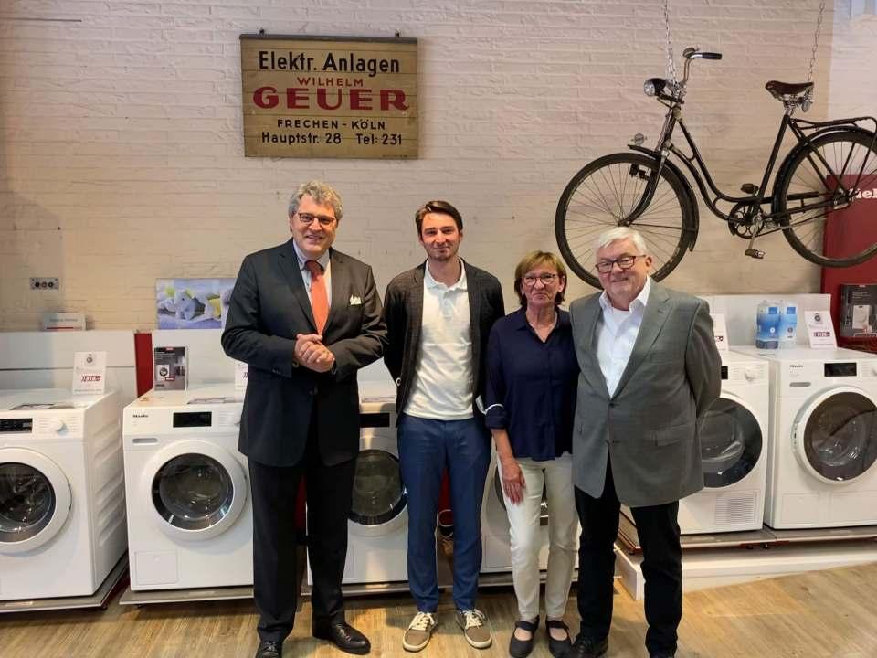 EP:Geuer hat eine große Verbundenheit zu Miele. Das Foto entstand vor einem alten Firmenschild aus den 1920er-Jahren im Ladenlokal in Frechen (v.l.): Dr. Reinhard Zinkann, Niklas Geuer und seine Eltern Helga und Wilhelm Wolfgang Geuer.